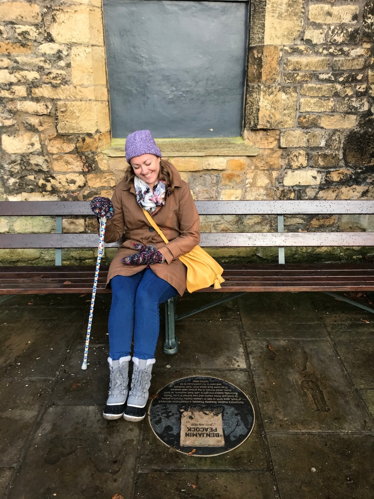 Anna sits on a bench. She is smiling at the floor as the person behind the camera makes her laugh. She has a lilac hat on, a khaki coat, blue jeans, grey snow boots, and a yellow handbag across her body. In her right hand is her multicoloured walking stick.
